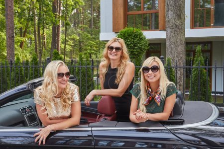 Vacation and people concept. Three happy blonde female friends wearing fashionable clothes in sunglasses sitting in a cabriolet car on summer trip vacation.