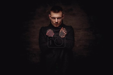 Tattooed young guy in a black jacket posing with crossed arms at the studio. Isolated on a dark textured background.