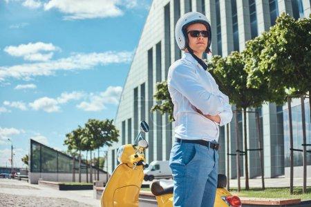 Photo pour Un bel homme confiant avec une coupe de cheveux élégante dans une chemise blanche, un jean, des lunettes de soleil et un casque de moto debout avec des bras croisés près du scooter italien classique jaune contre un gratte-ciel . - image libre de droit