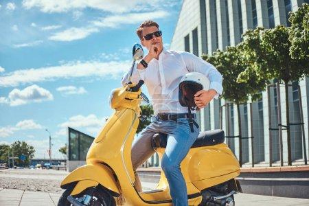 Photo pour Pensif bel homme avec une coupe de cheveux élégant habillé d'une chemise blanche, jeans et lunettes de soleil tient casque et la main sur le menton tout en étant assis sur un scooter italien classique jaune contre un gratte-ciel . - image libre de droit