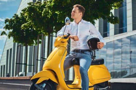 Photo pour Beau homme confiant avec une coupe de cheveux élégant habillé d'une chemise blanche, jeans et lunettes de soleil tient casque et assis sur un scooter italien classique jaune contre un gratte-ciel . - image libre de droit