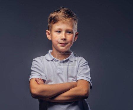 Photo pour Joli petit garçon vêtu d'un t-shirt blanc debout avec les bras croisés dans un studio. Isolé sur un fond gris . - image libre de droit