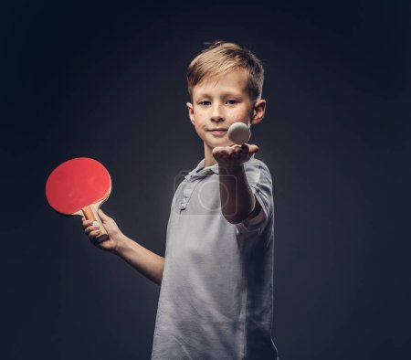 Redhead schoolboy dressed in a white t-shirt holds a ping-pong racquet and ball in a studio. Isolated on gray background.