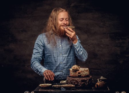 Photo for Portrait of a happy redhead hipster male with long hair and full beard dressed in a blue shirt, holds a small saucer with tea and enjoying the aroma. Isolated on a dark textured background. - Royalty Free Image