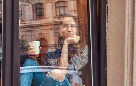 Pensive young redhead curly girl wearing casual clothes and glasses sitting on a window sill with hand on chin, holds a takeaway coffee.