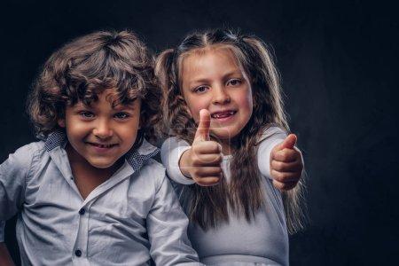 Photo pour Couple mignon d'un petit garçon aux cheveux bouclés et belle fille s'amuser dans un studio. Isolé sur le fond sombre texturé . - image libre de droit