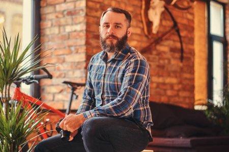 Photo pour Portrait d'un beau hipster barbu mâle en chemise polaire bleue et un jean tient une caméra alors qu'il est assis sur un tabouret en bois dans un studio avec un intérieur loft, en regardant une caméra . - image libre de droit