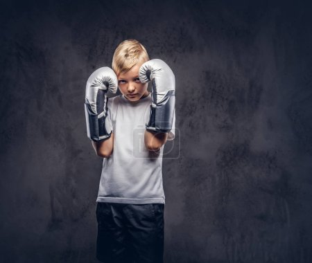 Little boxer with blonde hair dressed in a white t-shirt wearing boxing gloves, workout in a studio. Isolated on a dark textured background.
