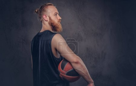 Portrait of a redhead basketball player in a black sportswear holding ball, isolated on a dark textured background.