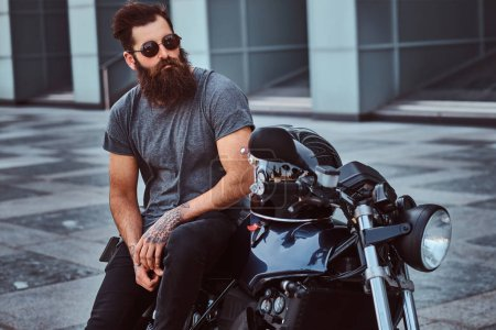 Portrait of a brutal bearded biker in sunglasses dressed in a gray t-shirt and black pants sitting on his custom-made retro motorcycle against a skyscraper