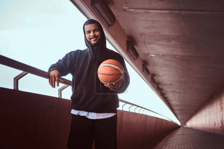 Smiling dark-skinned bearded guy dressed in a black hoodie and sports shorts leaning on a guardrail while standing with basketball, looking at a camera.