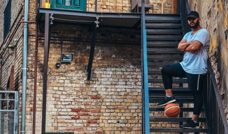African-American bearded streetball player in cap dressed in a sportswear holds a basketball standing with crossed arms on stairs in a ghetto.