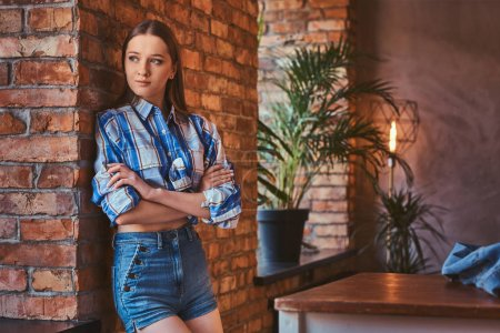 Portrait of a young hipster girl dressed in a shirt and jeans shorts crossed arms while leaning on a table in a room with loft interior.