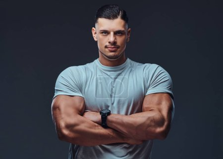 Photo for Close-up portrait of a muscular handsome bodybuilder in sportswear, standing with crossed arms in a studio, looking at the camera. Isolated on a gray background. - Royalty Free Image