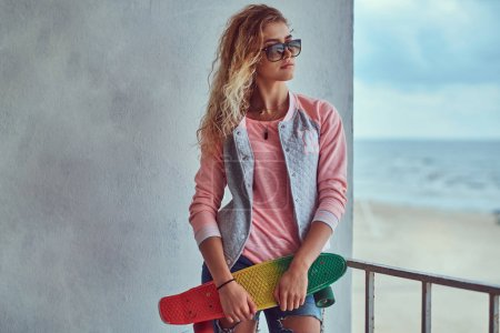 Photo for Portrait of a sensual young girl with blonde hair in sunglasses dressed in a pink jacket standing near a guardrail against a sea coast. - Royalty Free Image