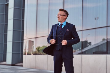 Confident businessman dressed in an elegant suit looking away and button up his jacket while standing outdoors against cityscape background.