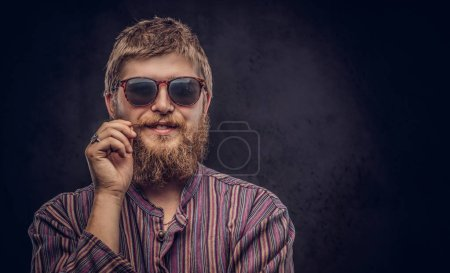 Happy hipster guy wearing sunglasses dressed in an old-fashioned shirt correct his mustache on a dark background.