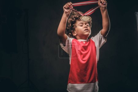 Cute little champion boy in sportswear puts on the gold medal. Isolated on the dark textured background.