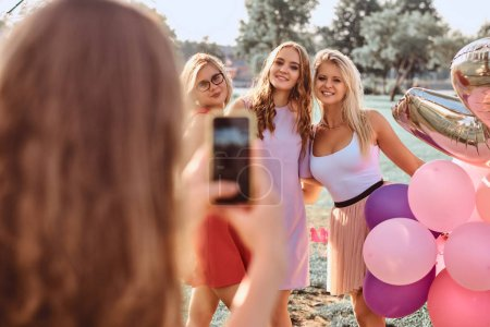 Joyful girlfriends are photographed together at picnic party outdoor. Scene of a celebrating a birthday at the outdoor park.