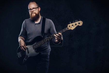 Photo pour Fuligule à tête rouge barbu musicien mâle porte des lunettes, vêtus d'un t-shirt gris, jouant à la guitare électrique. Isolé sur un fond texturé noir. - image libre de droit