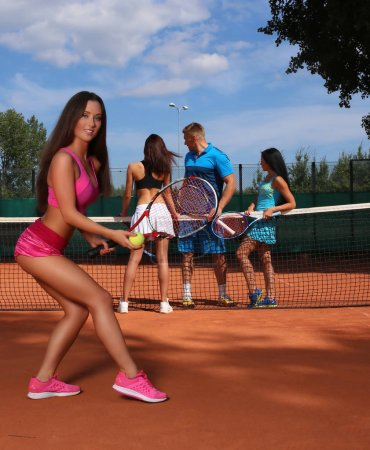 Handsome tennis instructor with two sexy girls on tennis training outdoors.