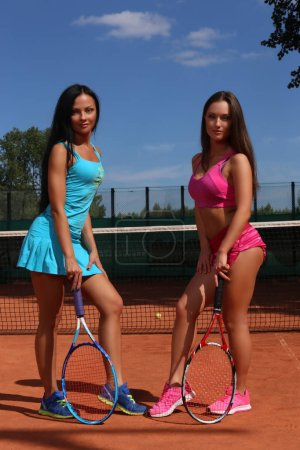 Two sexy girls in sportswear posing with tennis racquets on a tennis court.
