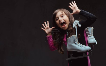 Playful little girl with an amused face dressed in sportswear holds ice skates. Isolated on dark textured background.