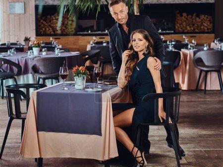 Photo pour Couple élégamment habillé - beau mâle élégant et charmante femme brune pendant la rencontre dans un restaurant de luxe . - image libre de droit