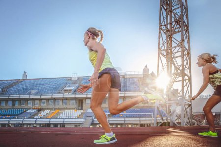Photo for Two female sprinter athletes running on the treadmill race during training in the athletics stadium. - Royalty Free Image