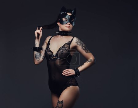 Sexy woman wearing black lingerie in BDSM cat leather mask and accessories posing on a dark background.
