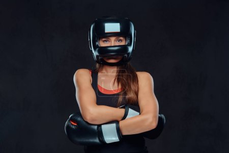 Close-up portrait of a female boxer wearing gloves and protective helmet posing in a studio. Isolated on dark textured background.