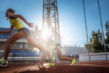 Two female sprinter athletes running on the treadmill race during training in athletics stadium.