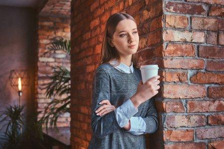 Photo pour Portrait d'une jeune fille vêtue d'une élégante robe grise appuyée contre un mur de briques tient une tasse de café à emporter regardant loin . - image libre de droit