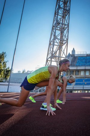 Two female sprinter athlete getting ready to start a race on a red running track in athletics stadium.