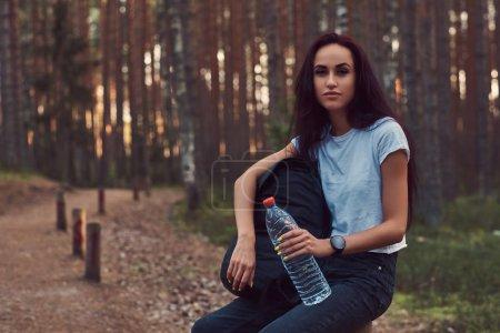 Photo pour Fille hipster touristique tient une bouteille d'eau, arrêté pour se reposer dans la belle forêt d'automne . - image libre de droit