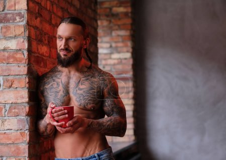 Stylish shirtless bearded male with muscular and tattooed body holds cup of coffee while leaning on a wall and looks out the window.