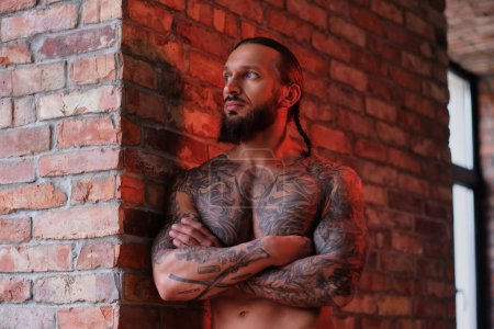 Stylish bearded male with the muscular and tattooed body leaning on a wall with crossed arms and looking out the window.