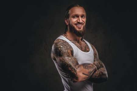 Photo for Smiling handsome bearded tattooed male in white shirt posing with crossed arms. Isolated on dark textured background. - Royalty Free Image