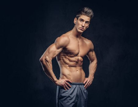 Handsome shirtless ectomorph bodybuilder with styl...