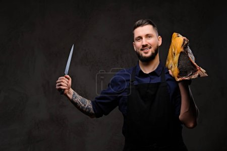 Smirking chef cook holds knife and large piece of ...