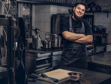 Photo pour Cuisinier barbu souriant en uniforme noir debout avec les bras croisés dans la cuisine . - image libre de droit