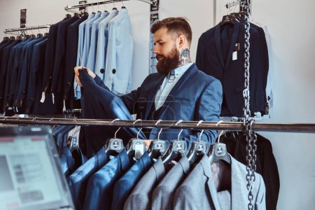 Photo for Elegantly dressed bearded male with tattoos on hands and neck chooses new costume in menswear store. - Royalty Free Image