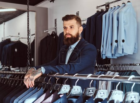 Photo for Pensive tattoed male with stylish beard and hair dressed in elegant suit standing in menswear store. - Royalty Free Image