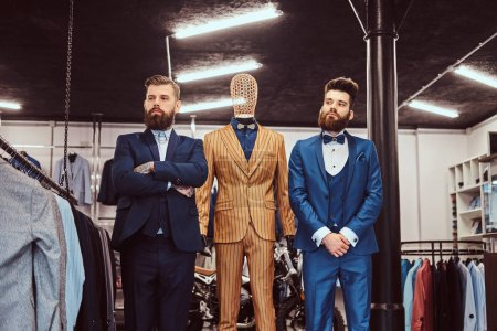 Two elegantly dressed shop assistants posing near mannequin in menswear store.