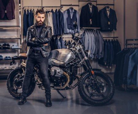 Photo pour Style, mode, concept de succès. Brutal mâle vêtu d'une veste noire posant avec les bras croisés près de moto de sport rétro au magasin de vêtements pour hommes . - image libre de droit