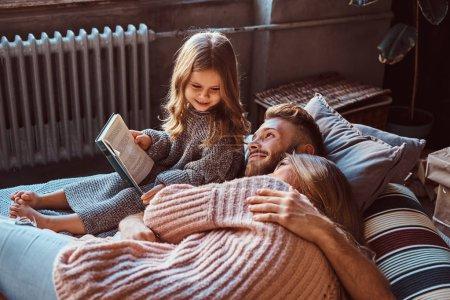 Photo pour Notion de famille. Maman, papa et livre de lecture fille ensemble en position couchée sur le lit. - image libre de droit