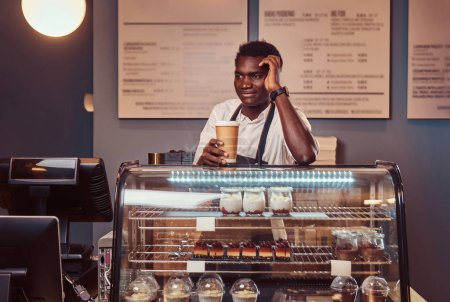 Portrait of a handsome African barista in white shirt and apron holds a cup of coffee and relaxing after workday at coffee shop.