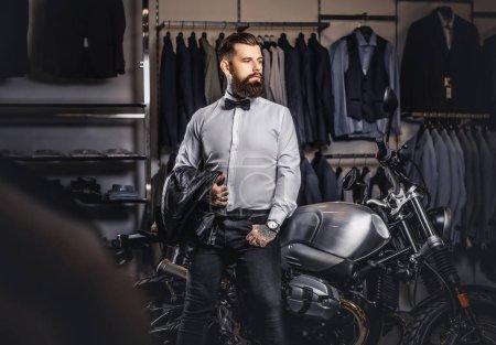 Elegantly dressed tattooed male with stylish beard holds black leather jacket posing near retro sports motorbike at the mens clothing store.