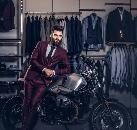 Handsome man with a stylish beard and hair dressed in vintage red suit posing near retro sports motorbike at mens clothing store.