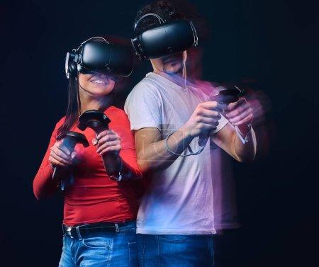 Foto de Amigos felices jugando videojuegos con gafas de realidad virtual con los controladores. Aislado sobre fondo oscuro. Foto con efecto de luz. - Imagen libre de derechos